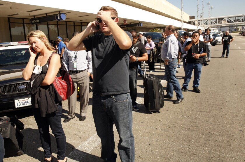 Travelers line the roadway outside terminals at LAX after a shooting at the airport in 2013. On Wednesday, officials will conduct a drill to test the facility's emergency response system.