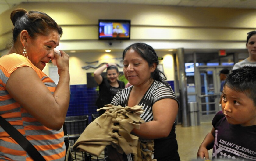 Yanira Lopez, left, wipes away tears after running into a friend from the Karnes City, Texas, detention center at a bus station in San Antonio last month.