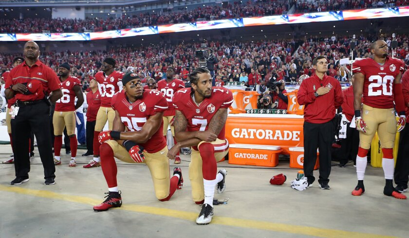 San Francisco 49ers quarterback Colin Kaepernick, center, and Eric Reid take a knee during the national anthem before the team's Sep. 12 game against the Rams.