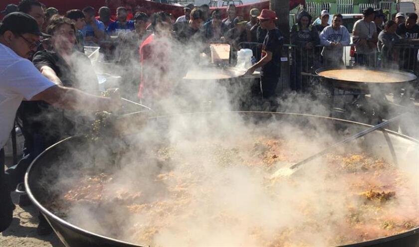 A poco más de un día de que se celebre la tradicional Nochebuena, más de 30 chefs locales e internacionales preparan hoy paella para los miles de migrantes centroamericanos que llegaron a la ciudad mexicana de Tijuana hace ya más de un mes, en el refugio El Barretal, un centro de espectáculos habilitado como albergue temporal en Tijuana (México). EFE