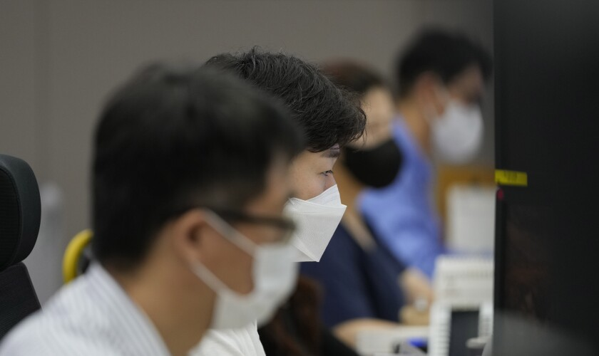 Currency traders watch computer monitors at the foreign exchange dealing room in Seoul, South Korea, Friday, July 9, 2021. Shares were mostly lower in Asia on Friday after stocks pulled back from their recent record highs on Wall Street as bond yields fell and investors turned cautious. (AP Photo/Lee Jin-man)