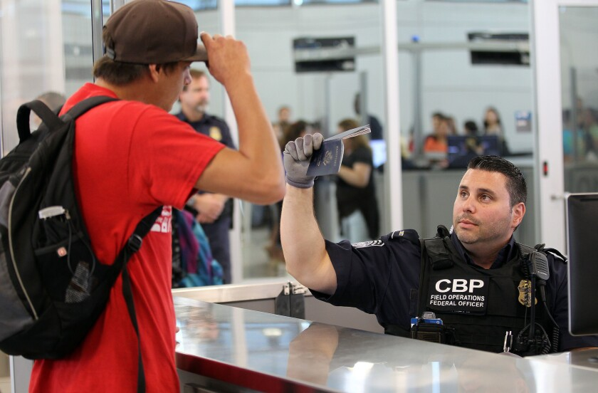 """At the San Ysidro Port of Entry, Esteban Santillan Gomez aimed his card at an electronic device that reads traveler information on chips embedded in passport cards, SENTRI and other """"trusted traveler"""" passes.  (John Gibbins / Union-Tribune)"""