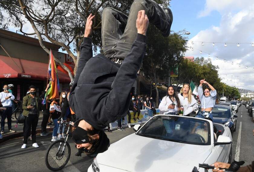 A man doing a backflip in front of a car on a busy street