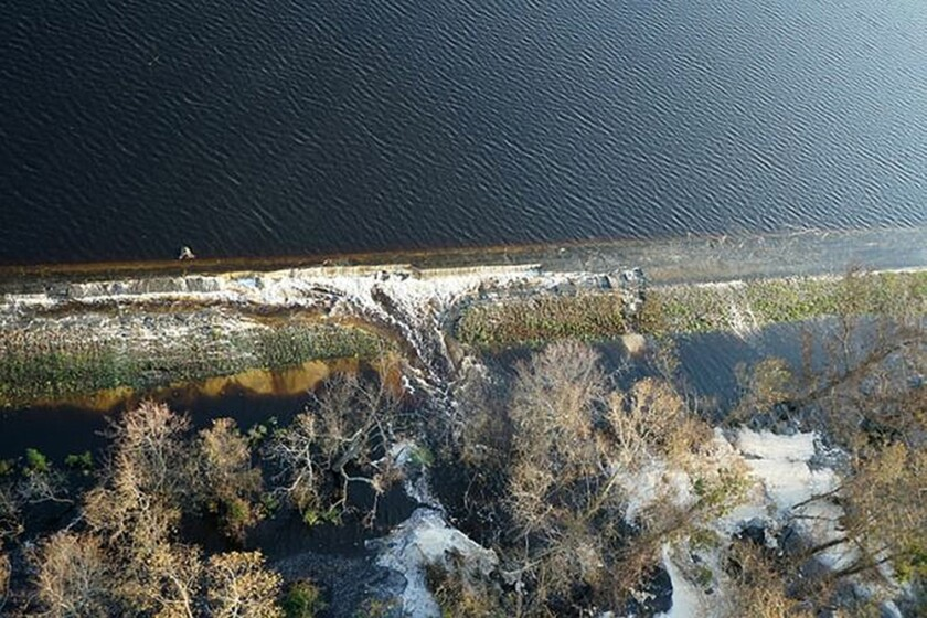 Gray material that Duke Energy characterized as lightweight coal combustion byproducts could be seen Friday floating on the top of the lake, near Wilmington, N.C.