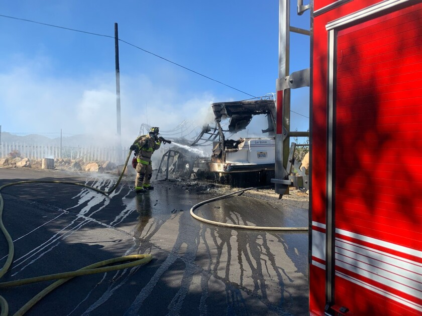 A firefighter douses an RV fire in Fallbrook Sunday.