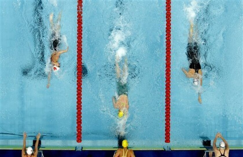 Australia's Kylie Plamer, center, swims against England's Joanne Jackson, right, and Canada's Genevieve Sammur during the 4x200 freestyle relay during the Commonwealth Games at the Dr. S.P. Mukherjee Aquatics Center in New Delhi, India, Wednesday, Oct. 6, 2010. (AP Photo/Victor R. Caivano)