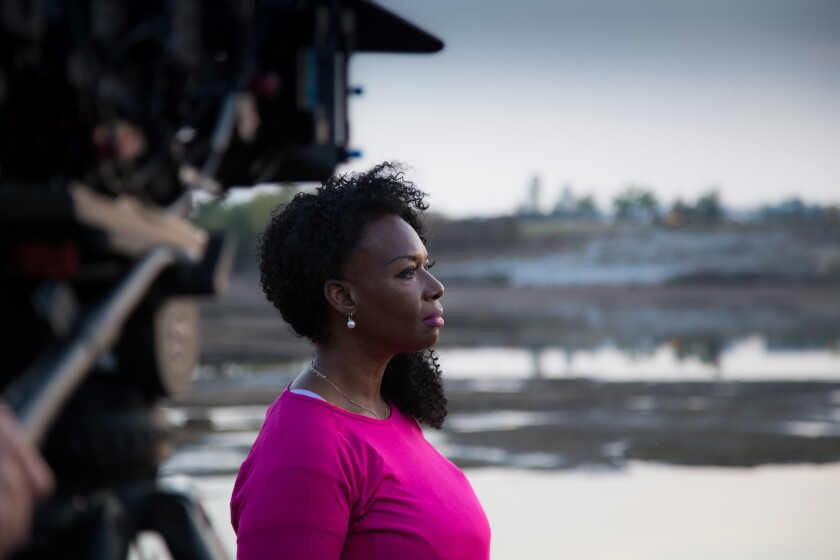 A woman in a pink shirt looks out over a segment of the Arkansas River as a camera observes
