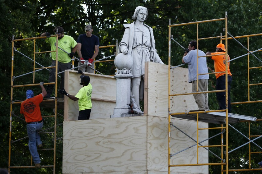 City workers cover a similar statue of Christopher Columbus in Philadelphia on Tuesday.