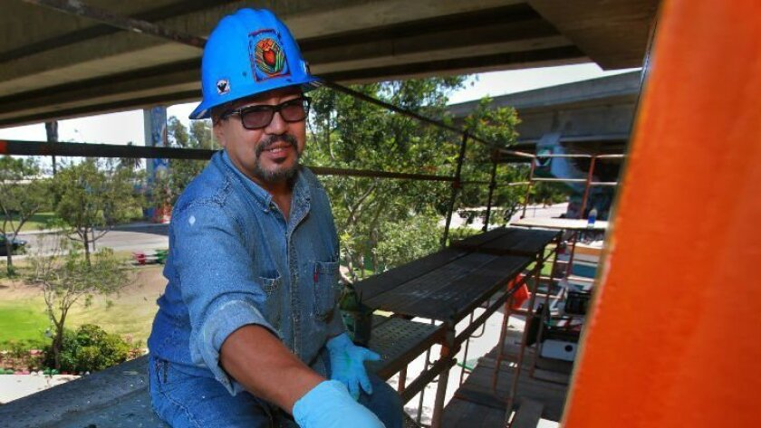 Mario Chacon, seen here in 2012 helping to restore historic Barrio Logan murals, will design and create the Lincoln Acres Elementary School project.