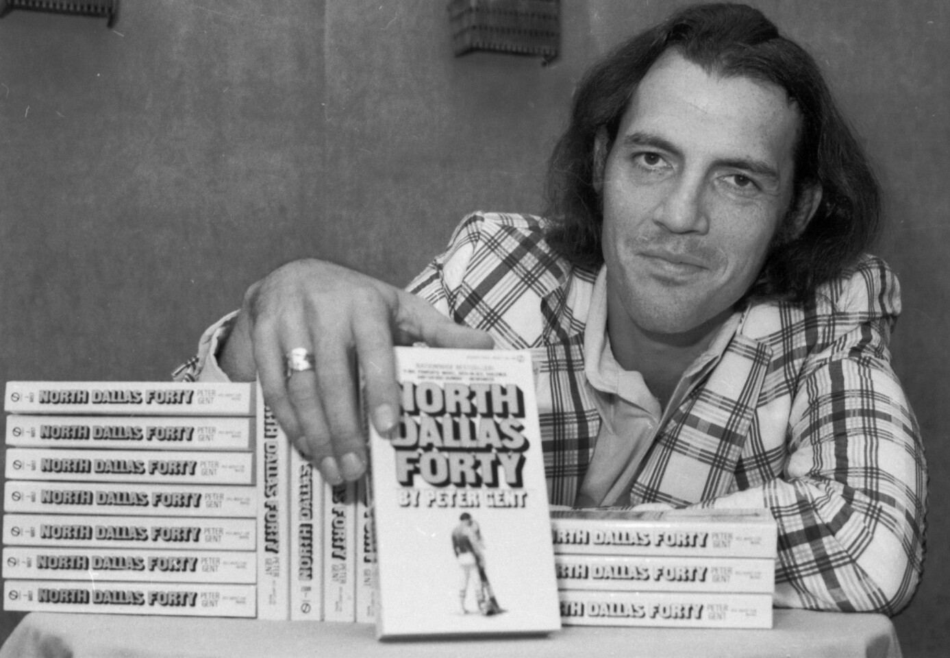 """Former Dallas Cowboy Peter Gent poses in 1974 with copies of """"North Dallas Forty,"""" his bestselling book about playing in the NFL. Gent wrote of hard-living, hard-hitting pro football players, but he wrote with style: """"It was late afternoon. In a last gasp the sun had burned away the gray sky and had disappeared into the Panhandle. The air had warmed some and the best part of the day remained. Being in Texas is a skin feeling, strongest this time of day.... I love Texas, but she drives her people crazy. I've wondered whether it's the heat, or the money, or maybe both. A republic of outlaws loosely allied with the United States, Texas survives, and survives quite well by breaking the rules."""""""
