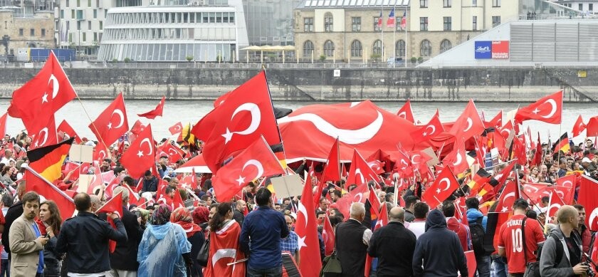 Turks hold national  flags during a demonstration in Cologne, Germany, Sunday, July 31, 2016.   Supporters of Turkish President Recep Tayyip Erdogan demonstrate in Cologne amid heavy police presence. Some 30,000 participants are expected at Sunday's demonstration, which comes amid tensions followin