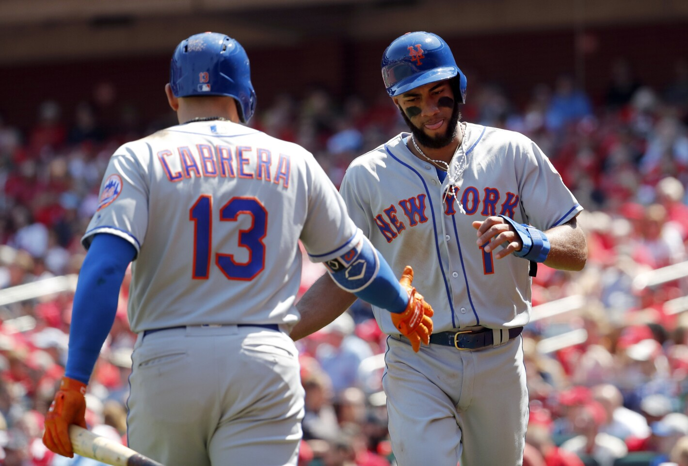 New York Mets' Amed Rosario, right, is congratulated by teammate Asdrubal Cabrera after scoring during the seventh inning of a baseball game against the St. Louis Cardinals Thursday, April 26, 2018, in St. Louis. (AP Photo/Jeff Roberson)