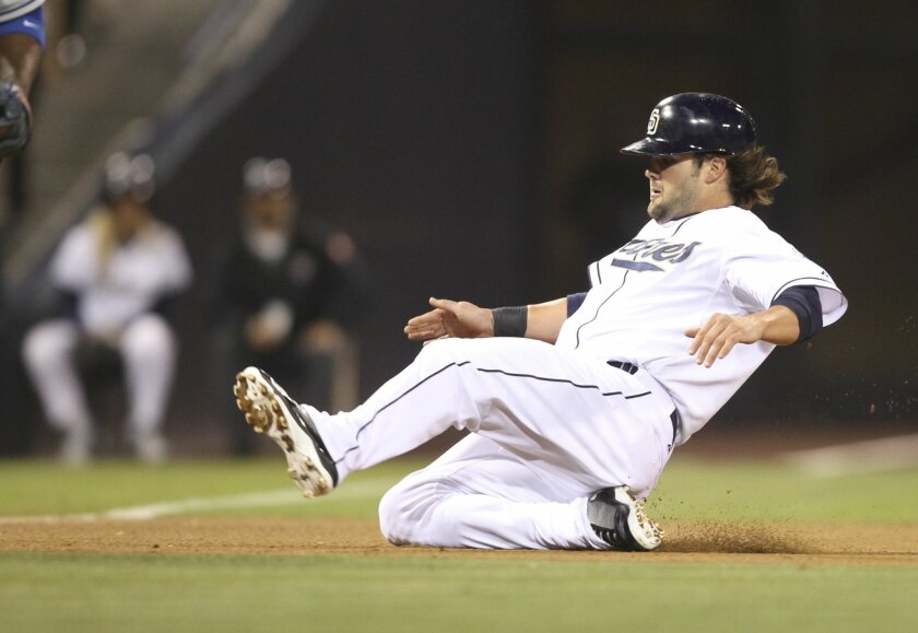 The Padres' Jaff Decker, who eventually scored, slides into third base in the seventh inning.