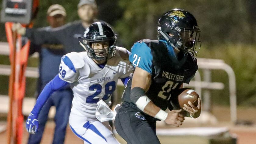 Valley Center running back Mateo Sinohui runs past Ramona defender Andrew Anguiano (28) on his way to a second-quarter touchdown in the Jaguars' win Friday over the Bulldogs.