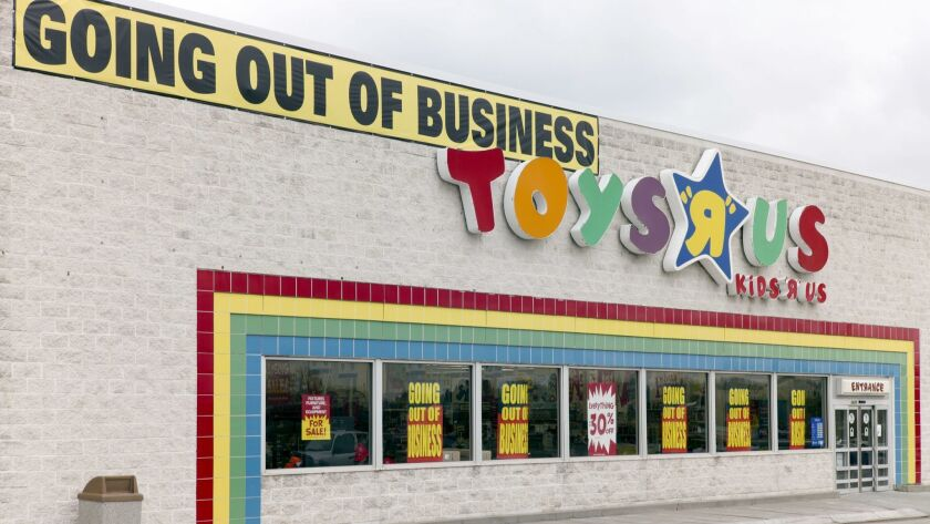 """A """"Going Out Of Business"""" sign hangs over the Toys R Us store logo in Omaha, Neb., Monday, April 9,"""