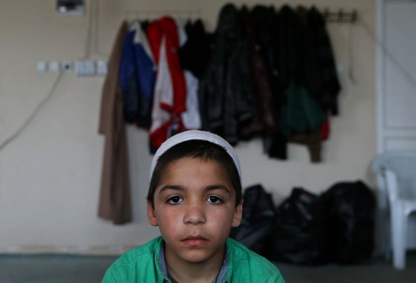 Fotografía del 19 de abril de 2015 de Ahmad, un niño de siete años y cuyos padres desaparecieron en Siria, mientras asiste a una clase de lecciones religiosas en un centro de enseñanzas islámicas diseñado para contrarrestar el adoctrinamiento del grupo Estado Islámico, en la ciudad de Sanliurfa, Turquía cerca de la frontera con Siria. (Foto AP/Hussein Malla)