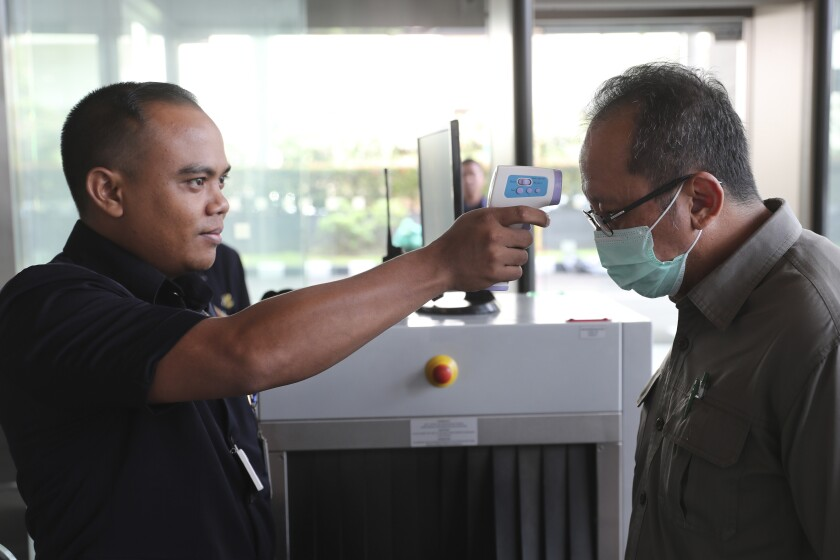 A security official checks the body temperature of a man at a building in Jakarta, Indonesia, Tuesday, March 3, 2020. Indonesia confirmed its first cases Monday, in two people who contracted the illness from a foreign traveler. (AP Photo/Achmad Ibrahim)