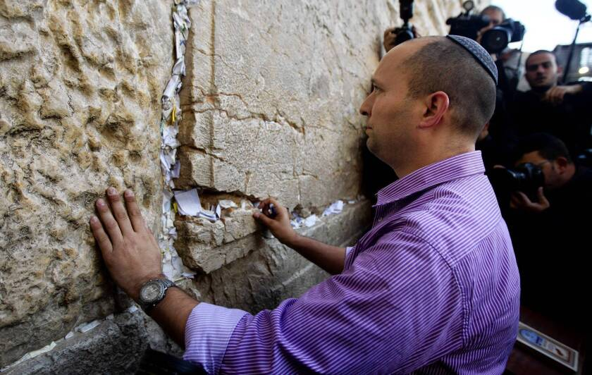 Naftali Bennett, head of the Jewish Home party, touches the Western Wall in Jerusalem's Old City in January.