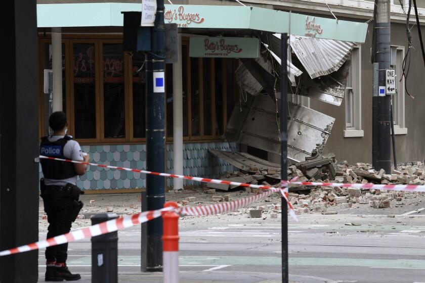 Un agente de policía cierra una intersección donde cayeron escombros sobre la calle después de un sismo