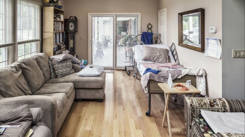 Raised Hospital Bed In Cluttered Private Residence Living Room