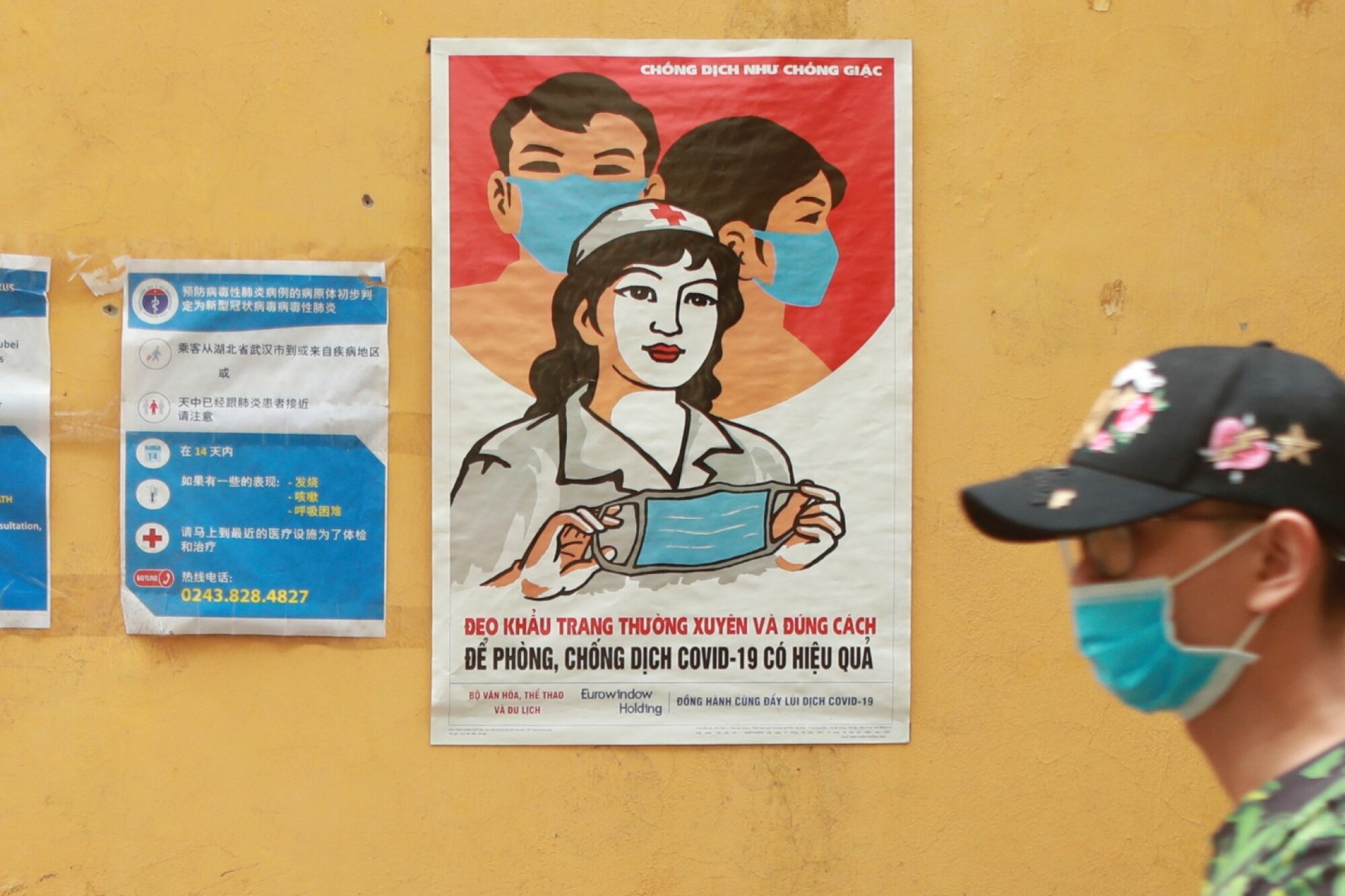 A man walks past a poster encouraging people to wear face masks correctly in Hanoi, Vietnam. The country began lifting its nationwide lockdown April 23.