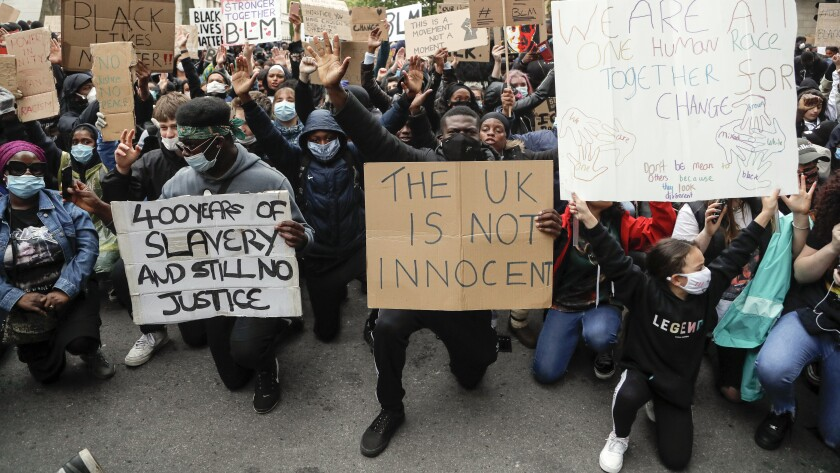 """FILE - In this file photo dated Saturday, June 6, 2020, demonstrators gather outside Downing Street during a Black Lives Matter march in London. A government inquiry, by a panel of experts, has concluded Wednesday March 31, 2021, that there is racism in Britain, but it's not a systematically racist country that is """"rigged"""" against non-white people, though many ethnic-minority Britons greeted that claim with skepticism. (AP Photo/Frank Augstein, FILE)"""