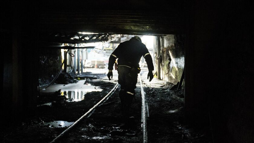 "In this Oct. 6, 2015 photo, a miner walks out of the Sewell ""R"" coal mine Tuesday, Oct. 6, 2015, in"