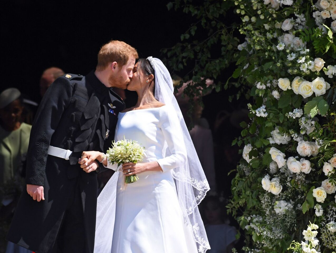 Meghan Markle and and Prince Harry kiss as they exit St. George's Chapel at Windsor Castle after their royal wedding ceremony on May 19.