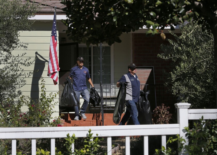 Police investigators and an Emergency Response crew clean up a house in La Cañada-Flintridge Monday morning, where an apparent murder/suicide took place on Sunday night.