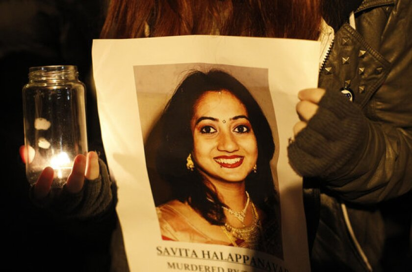 A woman holds a picture of Savita Halappanavar during a candle light vigil outside Belfast City Hall, Northern Ireland, on Thursday for Savita Halappanavar, who died of blood poisoning after suffering a miscarriage in Galway.
