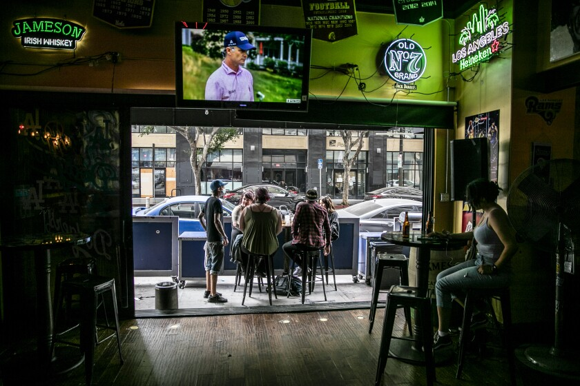 Patrons drink at an outside patio Sunday at the Down & Out sports bar in downtown L.A.
