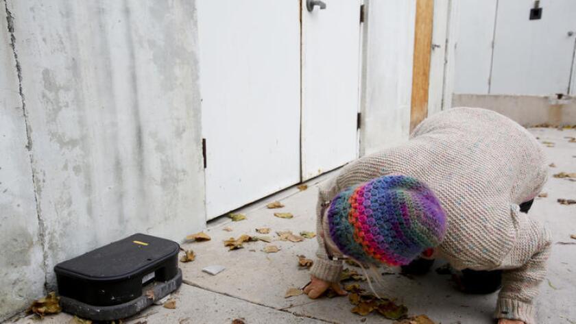 Kian Schulman checks the label on a rat trap by a business in Malibu.