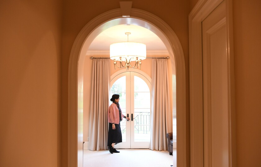 Real estate agent Dee Chou stands inside one of the eight bedrooms of an Arcadia house listed at $9.8 million. It has been on the market for two months.