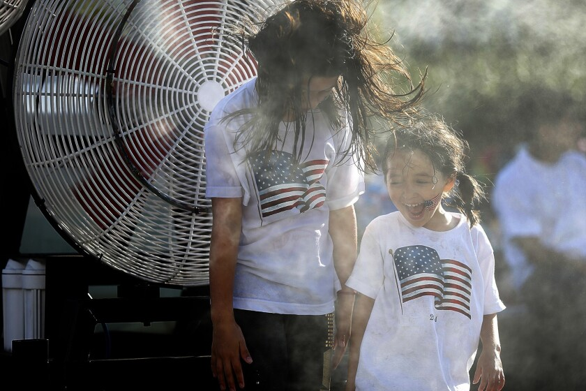Sisters Cherokee, 7, and Maya Lynne Spears, 4 of Los Angeles enjoy a misting station as they join thousands of people at the Grand Park Fourth of July Block Party in downtown Los Angeles.