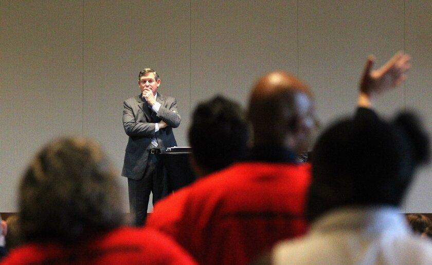 """California State University Chancellor Timothy White listens to faculty members wearing red shirts that read """"I don't want to strike, but I will"""" during a forum at San Diego State University on Wednesay."""