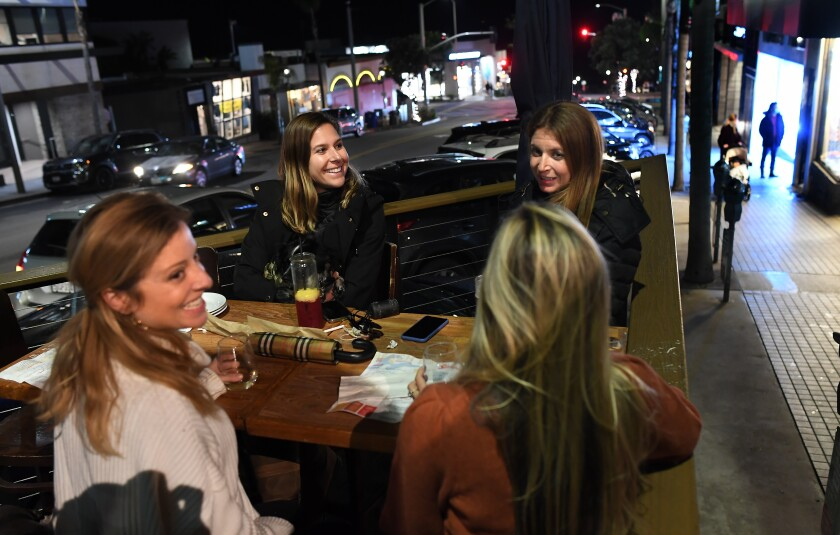 Four women sit at an outdoor restaurant table having drinks
