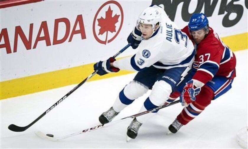 Montreal Canadiens' Gabriel Dumont reaches for the puck around Tampa Bay Lightning's Keith Aulie during the first period of an NHL hockey game on Thursday, April 18, 2013 in Montreal. (AP Photo/The Canadian Press, Paul Chiasson)