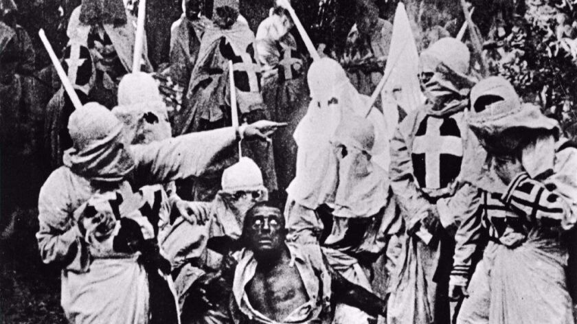 Actors costumed in the full regalia of the Ku Klux Klan chase down a white actor in blackface in a s