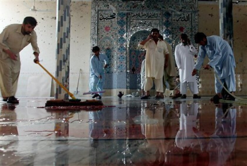 People wash the mosque floor after a suicide attack in Darra Adam Khel, 35 kilometers (21 miles) south of Peshawar, Pakistan, Friday, Nov. 5, 2010. A suicide bomber struck a mosque killing many people. official said. (AP Photo/Mohammad Sajjad)