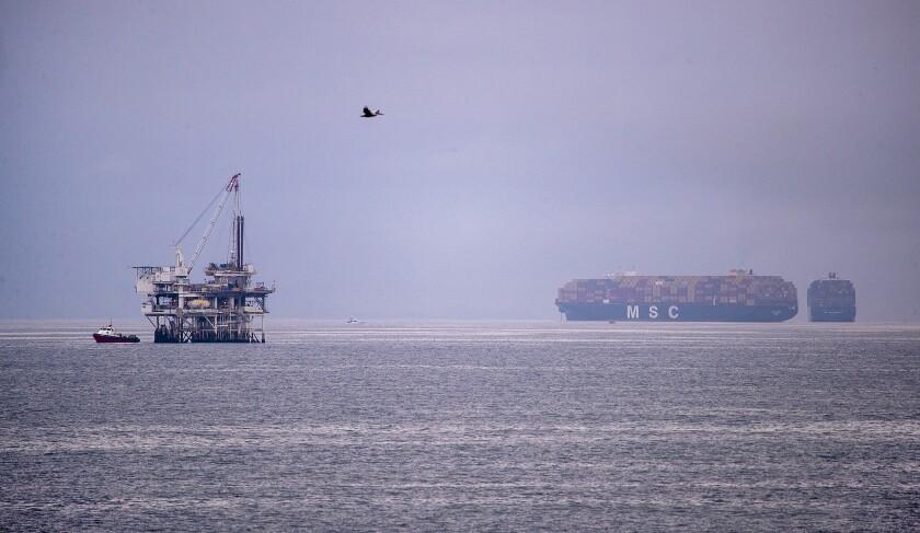 A pelican flies over an oil platform in the ocean