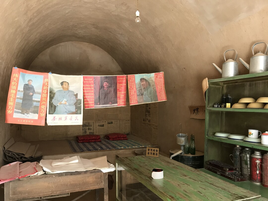 Posters of Mao Zedong hang a cave.