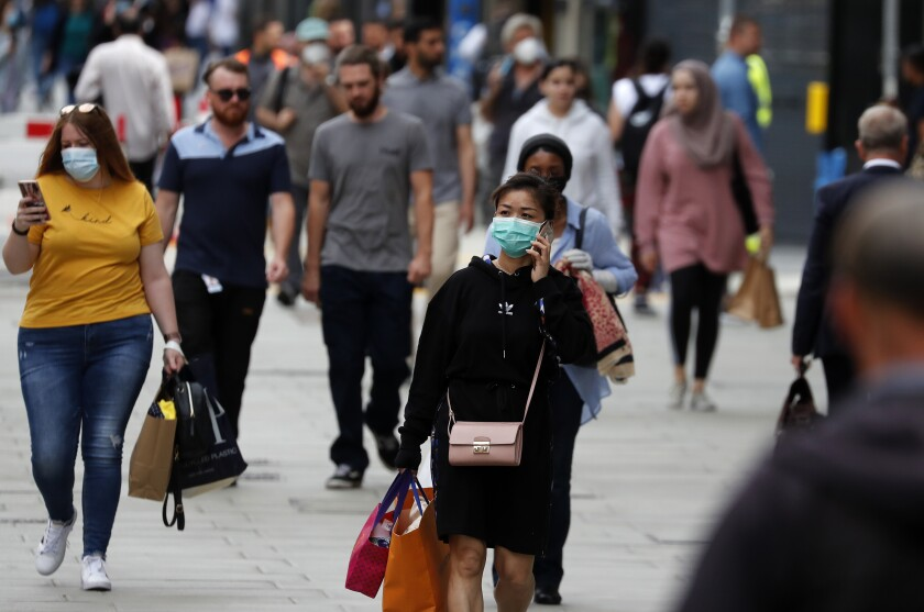 Shoppers, some wearing masks, walk along Oxford Street in London on Tuesday.