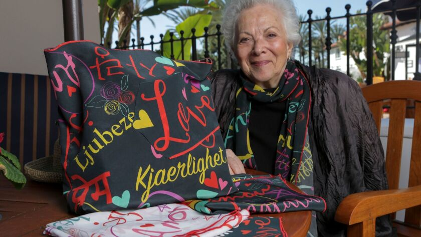 "Angela Coppola with her new line of scarves printed with the word ""love"" in several languages. photo"