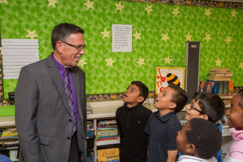 Superintendent Chris Oram chats with students, from left, Josue Huerta, Jared Benevides, Anthony Cervantes, Venson Bastier, and Nicole Tcha Binidi in their classroom. He retires June 30 after nearly 40 years of service to the National School District. Photo by David Hodges.