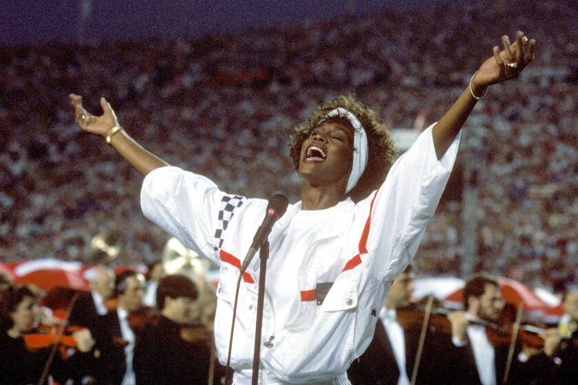 Whitney Houston, pictured singing at the Super Bowl in 1991, is among the artists due for induction in the Rock and Roll Hall of Fame, which announced it was postponing its annual ceremony.