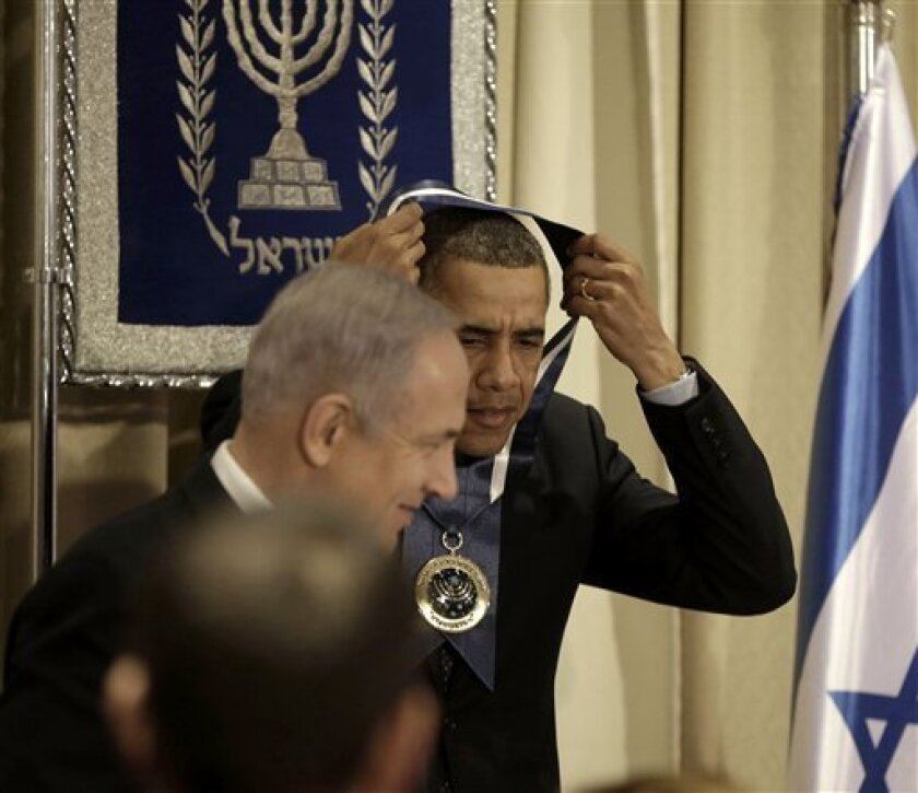 President Barack Obama, accompanied by Israeli Prime Minister Benjamin Netanyahu, left, removes his Israeli Medal of Distinction, which he received at the State Dinner at President's residence in Jerusalem, Israel, Thursday, March 21, 2013.  (AP Photo/Pablo Martinez Monsivais)