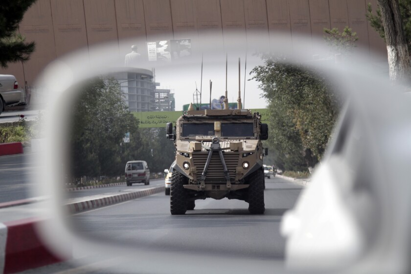 A U.S. armored vehicle is reflected in the mirror of a car in Afghanistan.