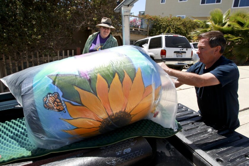Daniel Marion, who is founder Rainbarrelartist.com, delivers EarthFair organizer Carolyn Chase the rain barrel she ordered, which originally was a 50 gallon olive barrel from Italy destined for the dump, at her Pacific Beach home in San Diego on Wednesday.