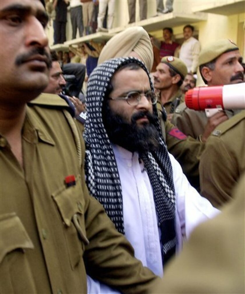 FILE – In this Dec. 16, 2002 file photo, Kashmiri man accused in the parliament attack Mohammed Afzal Guru, second right, is produced at a court in New Delhi, India. Afzal, convicted in the 2001 attack on India's Parliament, has been hanged in an Indian prison, a senior Indian Home Ministry officia