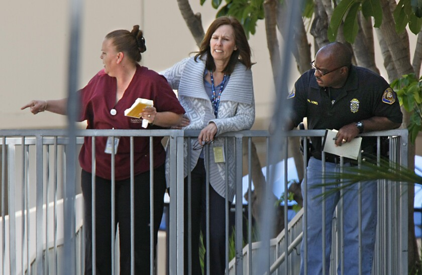 Long Beach Memorial Medical Center employees gather outside the walk-in emergency entry after a 2009 shooting. Hospitals are starting to hold training sessions for employees on what to do if a shooter walks in.
